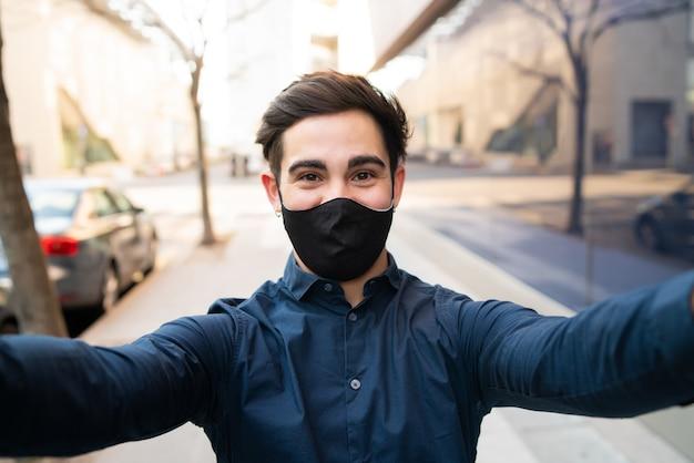 Porträt des jungen mannes, der schutzmaske trägt und ein selfie nimmt, während draußen auf der straße stehend