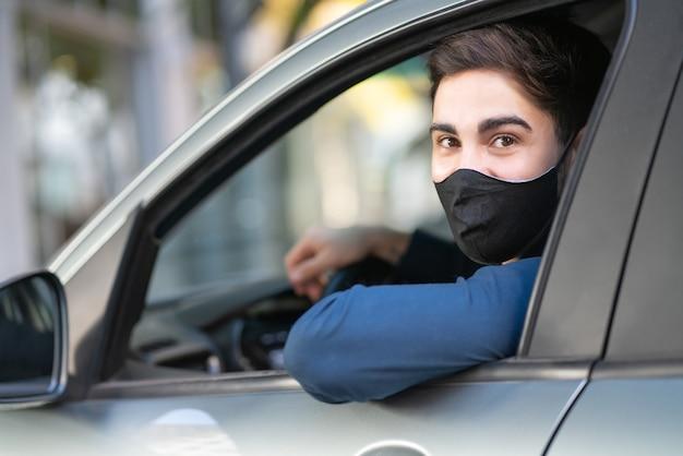 Porträt des jungen mannes, der sein auto fährt und gesichtsmaske trägt. neues normales lifestyle-konzept.