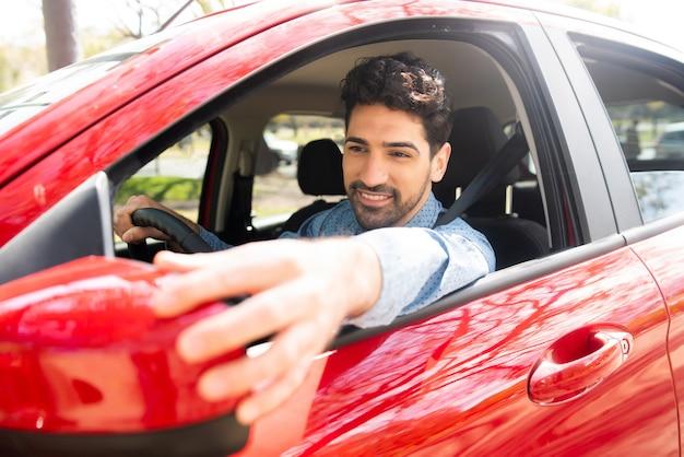 Porträt des jungen mannes, der sein auto fährt und rückspiegel bewegt.
