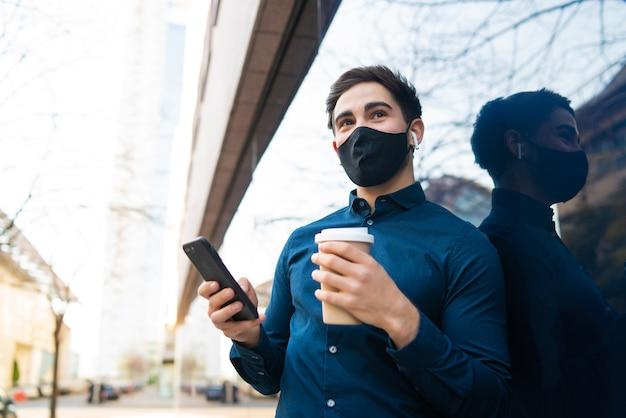 Porträt des jungen mannes, der sein handy benutzt und eine tasse kaffee hält, während er draußen auf der straße steht. neues normales lifestyle-konzept. stadtkonzept.