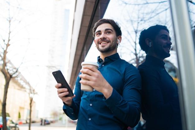 Porträt des jungen mannes, der sein handy benutzt und eine tasse kaffee hält, während er draußen auf der straße steht. stadtkonzept.