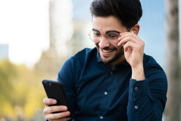 Porträt des jungen mannes, der sein handy benutzt, während er draußen auf der bank sitzt. stadtkonzept.