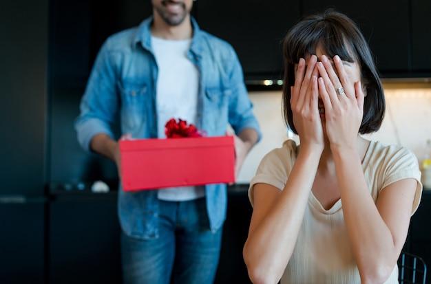 Porträt des jungen mannes, der seine freundin mit einer geschenkbox überrascht. feier und valentinstag konzept.