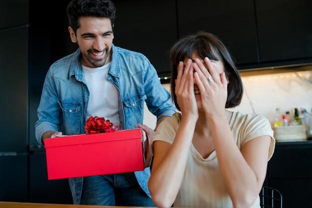 Porträt des jungen mannes, der seine freundin mit einer geschenkbox überrascht