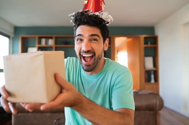 Porträt des jungen mannes, der seinen geburtstag auf einem videoanruf feiert und geschenke öffnet, während zu hause bleibt