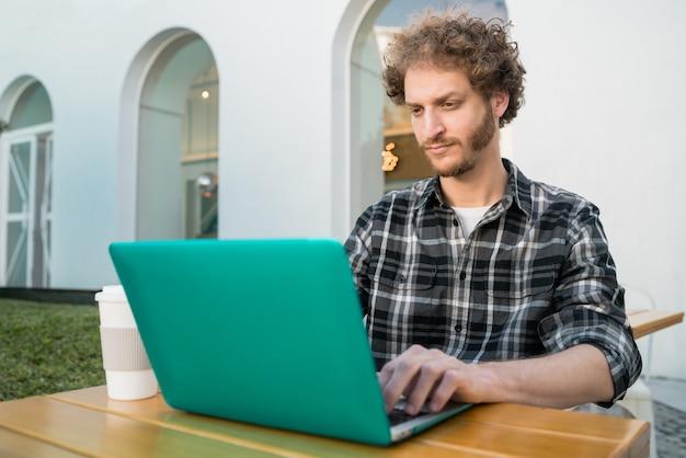 Porträt des jungen mannes, der seinen laptop benutzt, während er in einem café sitzt