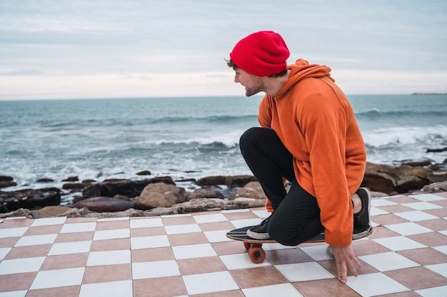 Porträt des jungen mannes, der spaß mit seinem skateboard hat und seine tricks mit meer im raum übt.
