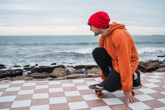 Porträt des jungen mannes, der spaß mit seinem skateboard hat und seine tricks mit meer übt