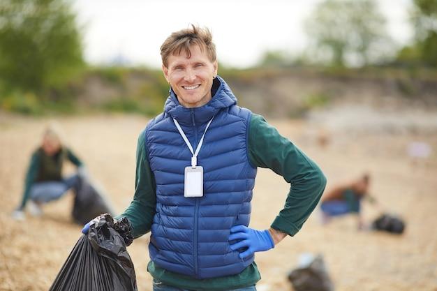 Porträt des jungen mannes, der tasche mit müll hält und an der kamera lächelt, während draußen steht