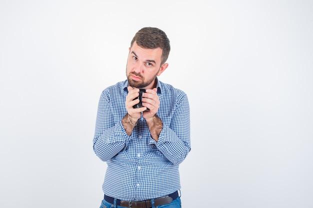 Porträt des jungen mannes, der tasse im hemd, in den jeans und in der zuversichtlichen vorderansicht hält
