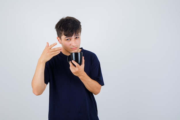 Porträt des jungen mannes, der tasse tee hält, im schwarzen t-shirt wegweisend und nachdenkliche vorderansicht schauend zeigt