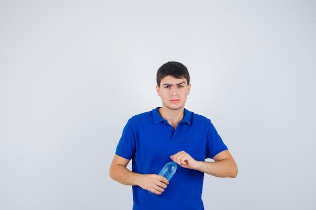 Porträt des jungen mannes, der versucht, plastikflasche im t-shirt zu öffnen und zögernde vorderansicht schaut