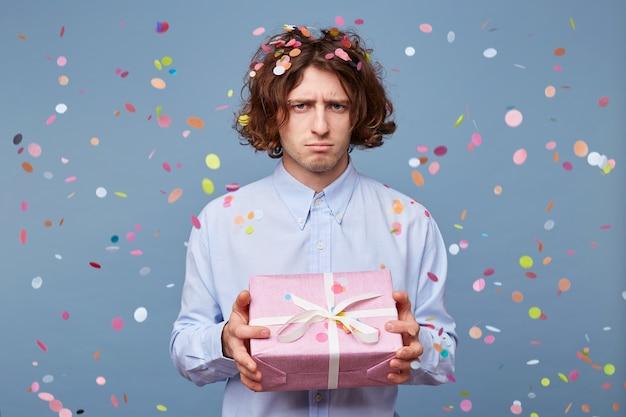 Porträt des jungen mannes, der verzierte rosa schachtel mit geschenk hält, sieht traurig aus
