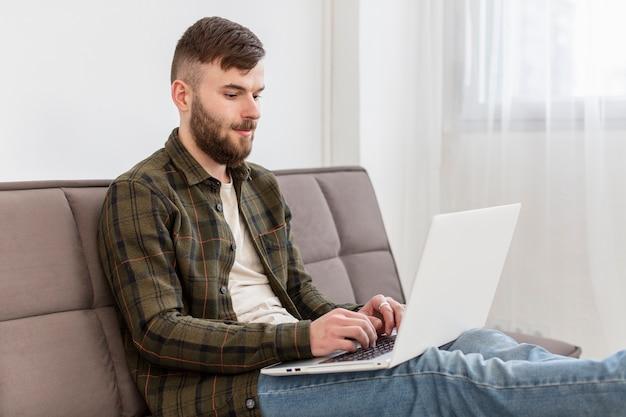 Porträt des jungen mannes, der von zu hause aus arbeitet