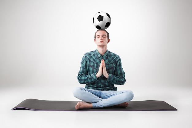 Porträt des jungen mannes, der yoga mit fußball praktiziert