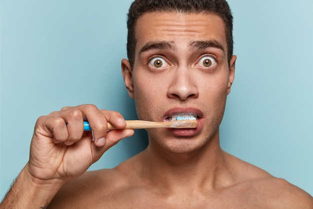 Porträt des jungen mannes, der zahnbürste hält