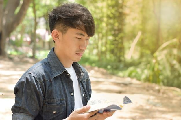 Porträt des jungen mannes ein buch im park am sommertag lesend.