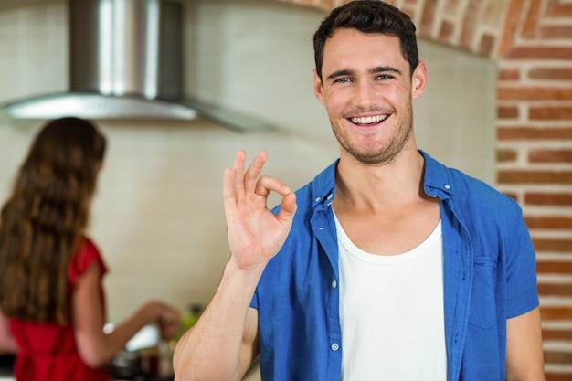 Porträt des jungen mannes gestikulierend in küche während frau, die auf ofen kocht