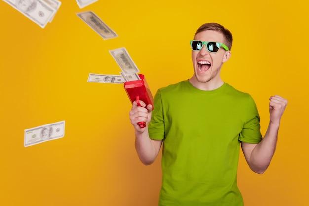 Porträt des jungen mannes glückliches positives lächeln, das große geldsummen einzeln auf gelbem farbhintergrund wegwirft
