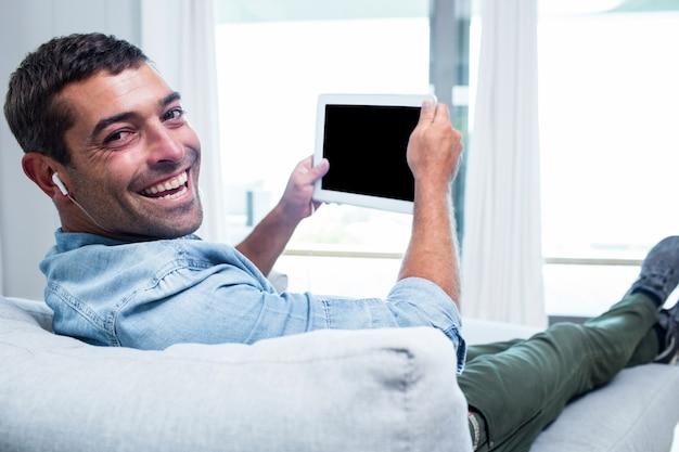 Porträt des jungen mannes hörend musik bei der anwendung der tablette