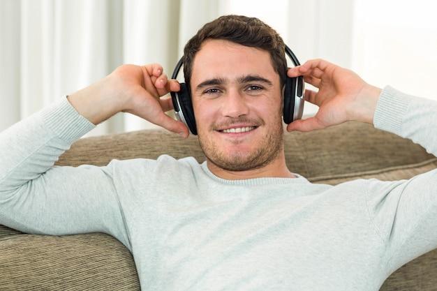 Porträt des jungen mannes hörend musik mit kopfhörern im wohnzimmer