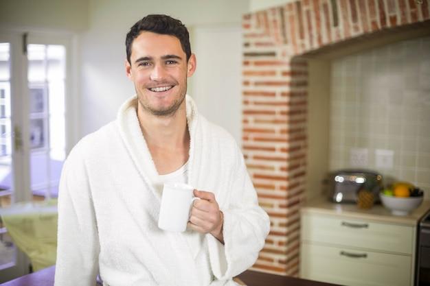 Porträt des jungen mannes im bademantel, der auf küchenarbeitsplatte sitzt und eine tasse tee trinkt