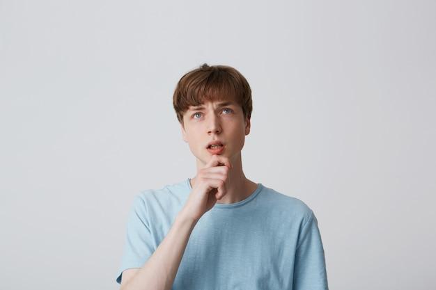 Porträt des jungen mannes im blauen t-shirt, hält arm am kinn und schaut auf