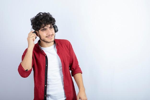 Porträt des jungen mannes im kopfhörer, der das lied über der weißen wand hört.