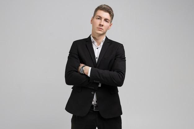 Porträt des jungen mannes im schwarzen anzug mit den armen gekreuzt