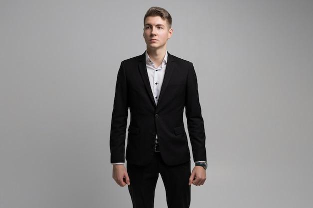 Porträt des jungen mannes im schwarzen anzug