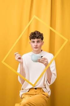 Porträt des jungen mannes in einer gelben szene hinter einem rahmen