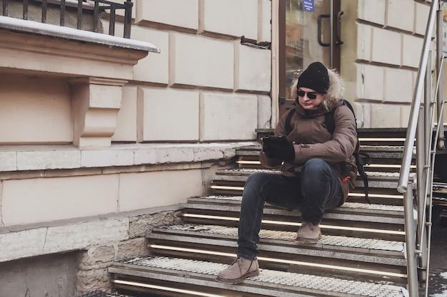 Porträt des jungen mannes in lässiger winterkleidung mit brille auf spaziergang in der stadt
