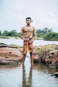 Porträt des jungen mannes in traditioneller tracht posiert in der natur in thailand