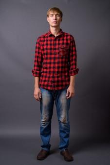 Porträt des jungen mannes in voller länge, der gegen grauen hintergrund steht