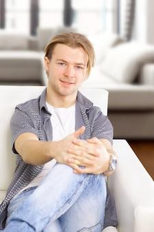 Porträt des jungen mannes in weiß auf sofa