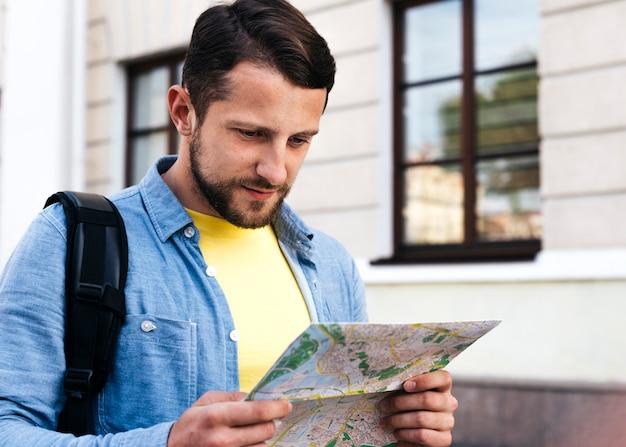 Porträt des jungen mannes karte während des reisens betrachtend