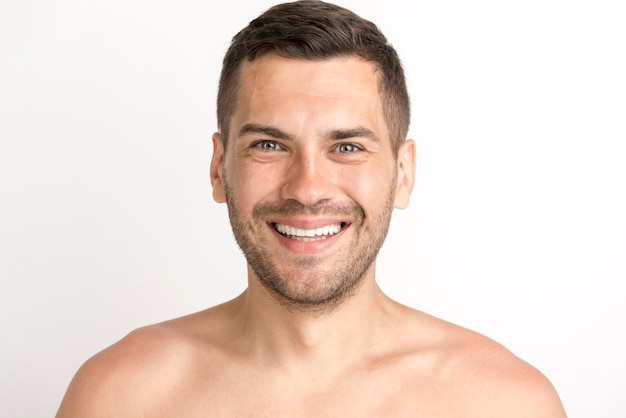 Porträt des jungen mannes lächelnd und die kamera betrachtend, die gegen weißen hintergrund steht