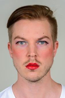 Porträt des jungen mannes mit bartstoppeln, die make-up tragen
