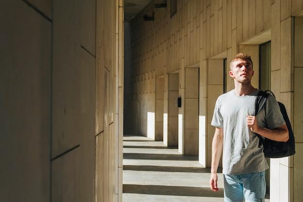 Porträt des jungen mannes mit dem rucksack, der weg schaut