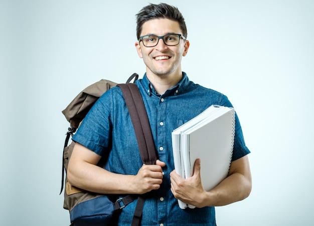 Porträt des jungen mannes mit dem rucksack lokalisiert