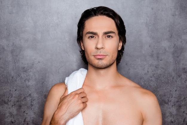 Porträt des jungen mannes mit dem schwarzen haar, das weißes handtuch der schultern hält