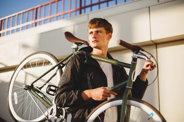 Porträt des jungen mannes mit den braunen haaren, die mit fahrrad stehen