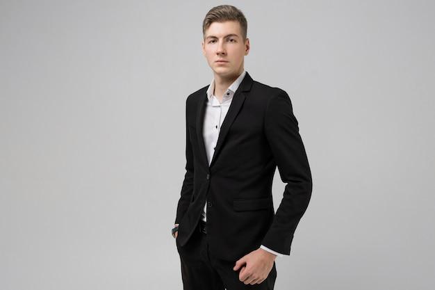 Porträt des jungen mannes mit den händen in den taschen im schwarzen anzug