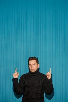 Porträt des jungen mannes mit ernstem gesichtsausdruck, der über blauem studio auftaucht