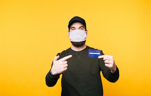 Porträt des jungen mannes mit gesichtsmaske, die auf kreditkarte zeigt