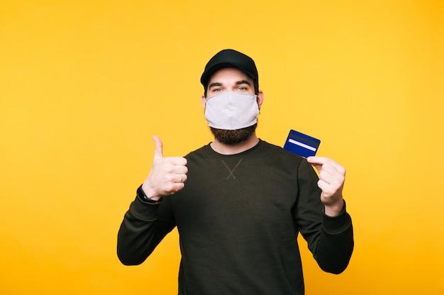 Porträt des jungen mannes mit gesichtsmaske, die kreditkarte zeigt und daumen oben zeigt