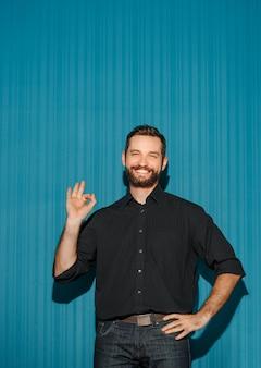 Porträt des jungen mannes mit glücklichem gesichtsausdruck, der ok auf blauem hintergrund zeigt