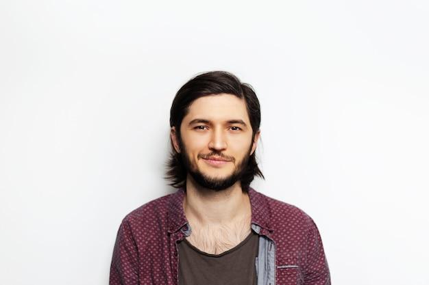 Porträt des jungen mannes mit langen haaren auf weiß.