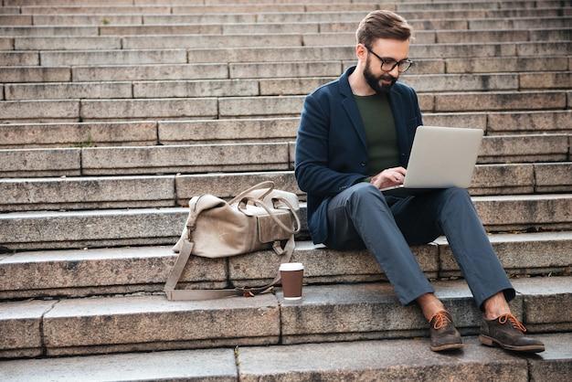 Porträt des jungen mannes mit laptop-computer