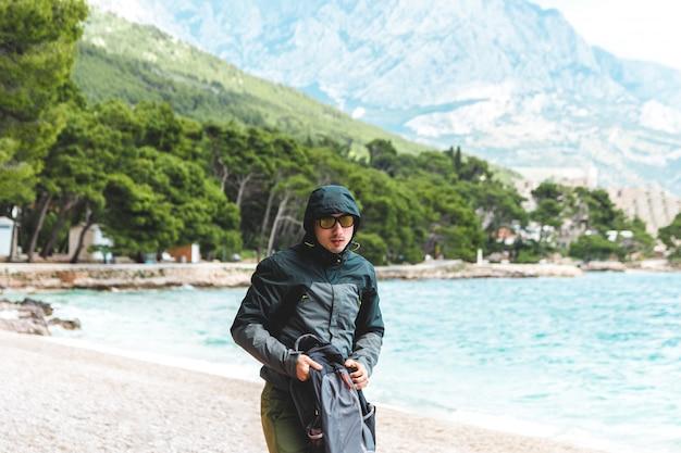 Porträt des jungen mannes mit regenmanteljacke am strand im sommer, der vom sturm wegläuft, der vom meer sich nähert. vorhersage des klimawandels für schlechtes wetter und kalte luft.